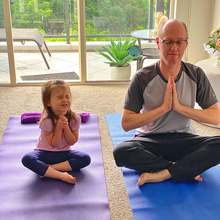Young girl and man doing yoga